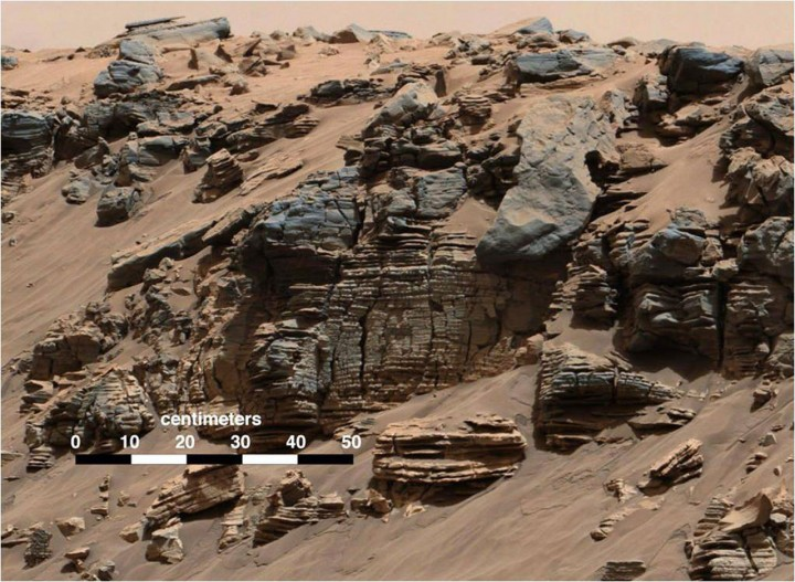 The image is from 'Hidden Valley' in Gale Crater on Mars. Very fine-grained sediments, which slowly fell down through the water, were deposited right at the bottom of the crater lake. The sediment plates at the bottom are level, so everything indicates that the entire Gale Crater may have been a large lake. Credit: NASA/JPL, MSSS)