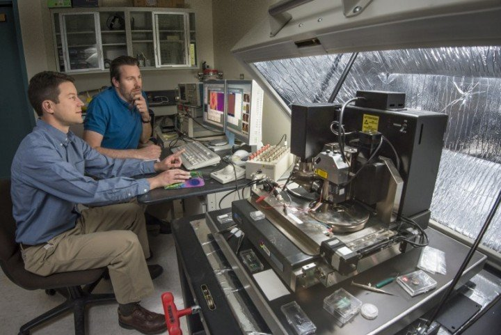 Sandia National Laboratories researchers Jon Ihlefeld, left, and David Scrymgeour use an atomic-force microscope to examine changes in a material's phonon-scattering internal walls, before and after applying a voltage. The material scrutinized, PZT, has wide commercial uses. (Photo by Randy Montoya)
