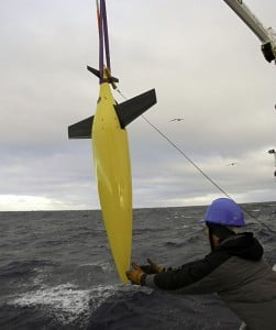A Seaglider is lowered from the ship to collect information below the surface. Image credit: Eric Rehm / UW