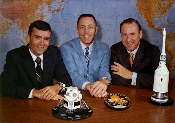 Astronauts Fred Haise (left), Jack Swigert and James Lovell pose with the Apollo 13 patch and spacecraft models the day before launch. Image Credit: NASA