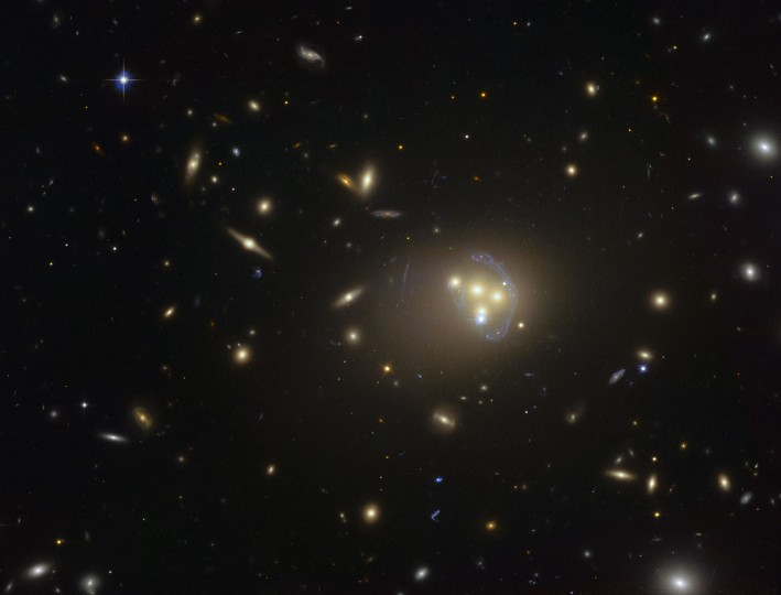 This image from the NASA/ESA Hubble Space Telescope shows the rich galaxy cluster Abell 3827. The strange blue structures surrounding the central galaxies are gravitationally lensed views of a much more distant galaxy behind the cluster. Observations of the central four merging galaxies have provided hints that the dark matter around one of the galaxies is not moving with the galaxy itself, possibly implying dark matter-dark matter interactions of an unknown nature are occuring. Credit: ESO
