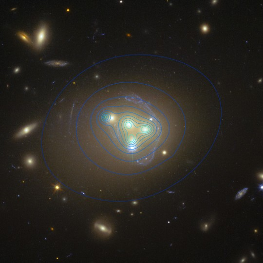 This image from the NASA/ESA Hubble Space Telescope shows the rich galaxy cluster Abell 3827. The strange pale blue structures surrounding the central galaxies are gravitationally lensed views of a much more distant galaxy behind the cluster. The distribution of dark matter in the cluster is shown with blue contour lines. The dark matter clump for the galaxy at the left is significantly displaced from the position of the galaxy itself, possibly implying dark matter-dark matter interactions of an unknown nature are occuring. Credit: ESO/R. Massey