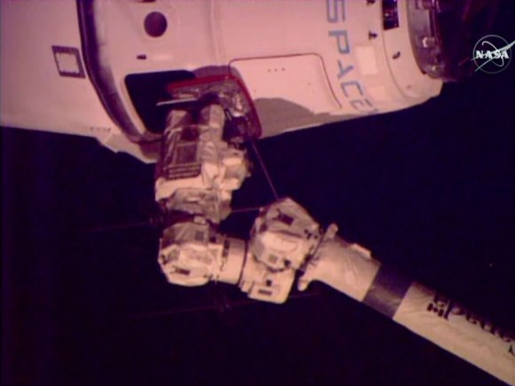 The SpaceX Dragon space freighter is in the grips of the Canadarm2 robotic arm. Credit: NASA TV