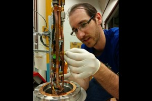 UW postdoc Martin Fertl connects wires for a small coil that is a magnetic trap for electrons. This apparatus is the insert that goes inside the superconducting magnet. Image credit: UW
