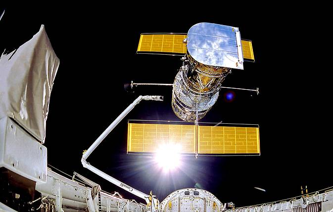 NASA's Hubble Space Telescope is suspended in space by Discovery's Remote Manipulator System following the deployment of part of its solar panels and antennae on April 25, 1990. Image Credit: NASA