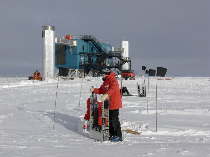Jason Koskinen at the South Pole. In the background is the IceCube Lab. All data from the instruments deep down in the ice comes up through the two 'towers' and into the computer center, where the first analyses are done. (Credit: T. Waldemaier)