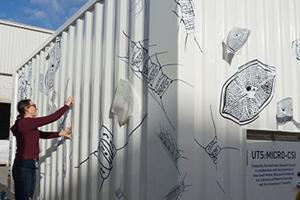 Dr Doblin applies marine-inspired decals to the container lab. Photo: An Marosszeky