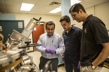 """Assistant professor Jagannathan Rajagopalan (right) is pictured in his Arizona State University laboratory with engineering graduate students Rohit Sarkar (left) and Ehsan Izadi, who assist with research to better understand the relationship between the microstructure and mechanical behavior of metals and alloys. The National Science Foundation is helping to support Rajagopalan's project to develop """"shape-memory"""" metal alloys. Photo by: Jessica Hochreiter/ASU"""