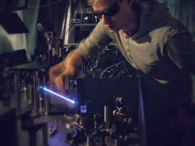 On the light catapult: Jan-Christoph Deinert adjusts the blue laser that researchers at the Fritz Haber Institute use to hurl electrons from a copper plate into a thin amorphous layer of ice serving as a model for liquid water. In their experiments, they are investigating how the electron is solvated in it. © Clemens Richter / Fritz Haber Institute