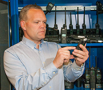 Dereck Orr with a variety of radios and cell phones used in NIST's public safety communications research. A new NIST report outlines research needed on location-based services—applications such as GPS that can improve situational awareness for emergency responders. Image credit: Burrus/NIST