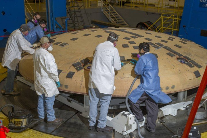 Engineers from NASA's Ames Research Center in Moffett Field, California, and NASA's Marshall Space Flight Center in Huntsville, Alabama, remove segments of a heat-resistant material called Avcoat from the surface of the Orion heat shield, the protective shell designed to help the next-generation crew module and its future occupants withstand the heat of atmospheric reentry. The work is being conducted in the seven-axis milling machine facility at Marshall. Credits: NASA/MSFC/Emmett Given