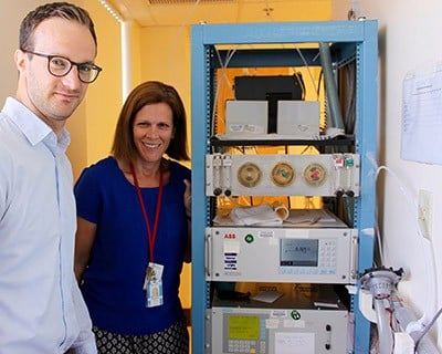 Lead researchers Drs. Martin Reinhardt and Susanne Votruba stand next to the carbon dioxide and oxygen analyzers, and outside the whole-room indirect calorimeter. The analyzers measured the study participants' energy expenditure while they were inside the calorimeter. Image credit: Enrique Diaz