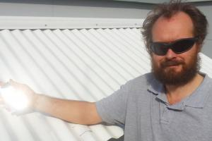 Dr Angus Gentle holding a piece of the special material over an existing cool roof used in testing. Picture supplied