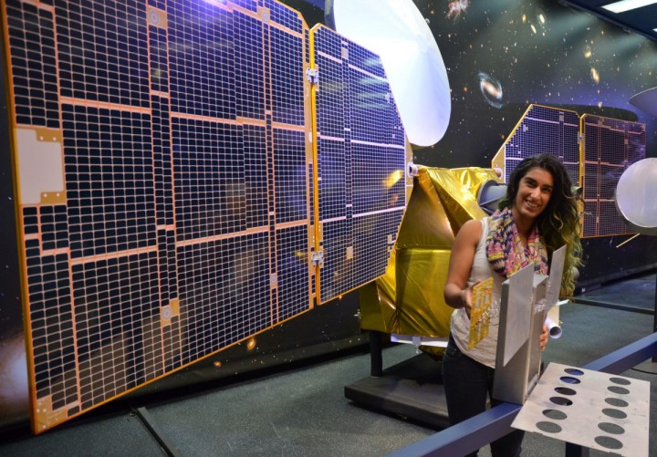 The full-scale mock-up of NASA's MarCO CubeSat held by Farah Alibay, a systems engineer for the technology demonstration, is dwarfed by the one-half-scale model of NASA's Mars Reconnaissance Orbiter behind her. Credits: NASA/JPL-Caltech