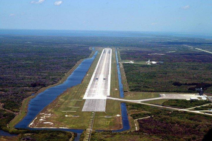 This aerial photo of the runway at the KSC Shuttle Landing Facility looks north. Longer and wider than most commercial runways, it is 15,000 feet long, with 1,000-foot paved overruns on each end, and 300 feet wide, with 50-foot asphalt shoulders. The runway is used by military and civilian cargo carriers, astronauts' T-38 trainers, Shuttle Training Aircraft and helicopters, as well as the Space Shuttle. Credits: NASA