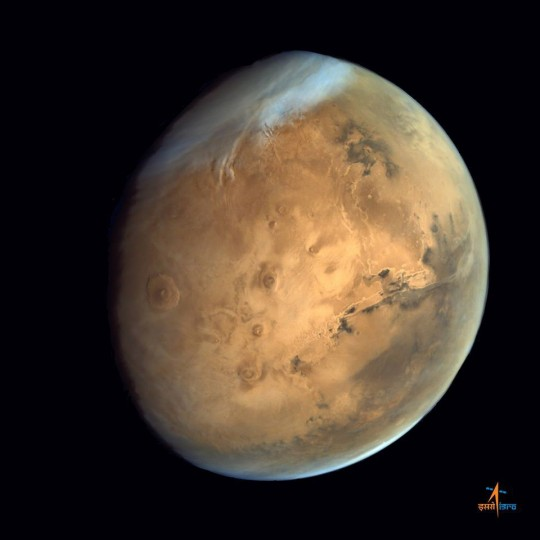 Olympus Mons, Tharsis Bulge trio of volcanoes and Valles Marineris from ISRO's Mars Orbiter Mission. Note the clouds and south polar ice cap. Credit: ISRO