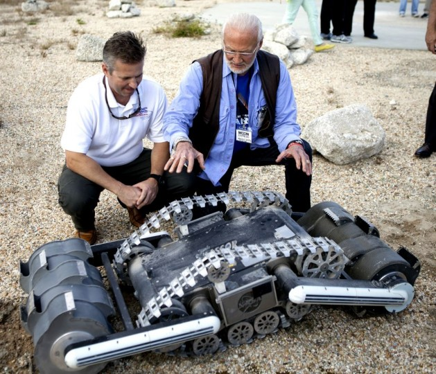 Rob Mueller, NASA senior technologist in the Surface Systems Office at the Kennedy Space Center, left, talks with former NASA Gemini and Apollo astronaut Buzz Aldrin during a demonstration of the Regolith Advanced Surface Systems Operations Robot, or RASSOR. The robot has been tested at Kennedy's Swamp Works. A similar spacecraft could be used to collect samples or excavate a landing pad for future landers. Credits: NASA/Ben Smegelsky