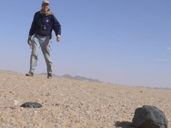 "On Feb. 28, 2009, Peter Jenniskens (SETI/NASA), finds his first 2008TC3 meteorite after an 18-mile long journey. ""It was an incredible feeling,"" Jenniskens said. The African Nubian Desert meteorite of Oct 7, 2008 was the first asteroid whose impact with Earth was predicted while still in space approaching Earth. 2008TC3 and Chelyabinsk are part of the released data set. (Credit: NASA/SETI/P.Jenniskens)"