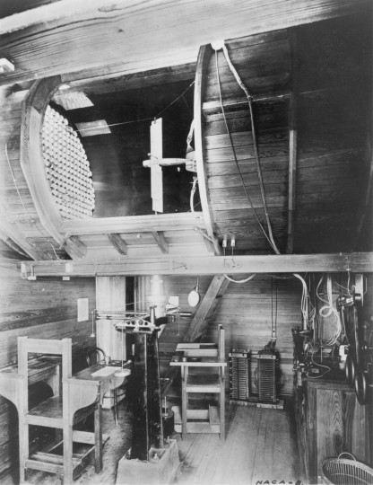"The 5 foot diameter circular test section and control room of NACA Tunnel No. 1. A Curtiss ""Jenny"" model can be seen mounted in the test section. Both a real JN4H and a highly accurate model were put through identical tests. The NACA engineers used this data to make the necessary corrections to the wind tunnel. Credits: NASA"
