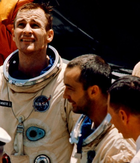 Gemini IV astronauts Ed White, left, and Jim McDivitt talk to officials on the USS Wasp recovery aircraft carrier on June 7, 1965. Credits: NASA
