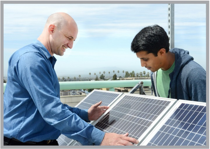 Eric Brewer and graduate student, Achintya Maduri, inspect solar panels used with a prototype power microgrid to provide electric power to homes in rural regions of the developing world. Photo: Peg Skorpinski.