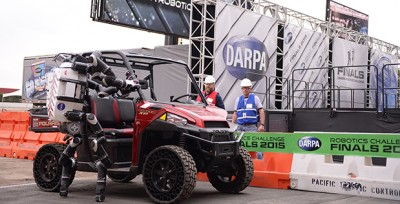 Robosimian, a robot created by NASA's Jet Propulsion Laboratory, exits the vehicle it had just driven as part of the DARPA Robotics Challenge (DRC) Finals.