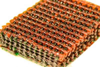 Photo shows the open lattice of 3-D printed material, with materials having different characteristics of strength and flexibility indicated by different colors. Courtesy of the researchers