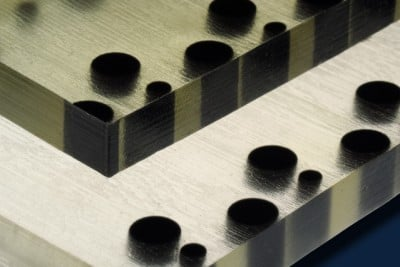 Polymer material produced by a 3-D printer includes soft, flexible material (clear or lighter tone) with particles of hard material (black) embedded, in predetermined arrangements. When the material is compressed, its surface become bumpy in a pattern determined by the hard particles. Photo: Felice Frankel