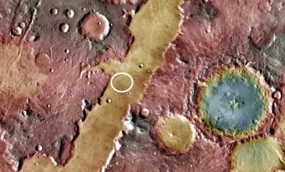 The search for impact glass A possible Martian site (white circle) is the Nili Fossae trough. The blue-tinted Hargraves crater at the right (blue indicates a low topography) is known to contain impact glass. Image: NASA/JPL-Caltech/Arizona State University