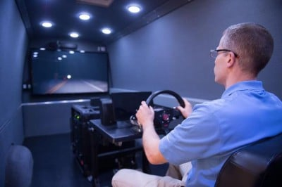 Andrew Veit, program manager of the UI's National Advanced Driving Simulator (NADS), demonstrates the organization's miniSim portable driving simulator. Image credit: Tim Schoon.
