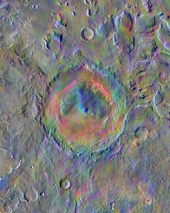 Nearly a hundred miles wide, Gale Crater, home to Mars rover Curiosity, shows a new face in this mosaic image made using data from the Thermal Emission Imaging System. The colors come from an image-processing technique that displays mineral differences in surface materials in false colors. For example, wind-blown dust appears pale pink and olivine-rich basalt looks purple. The bright pink on Gale's floor appears due to a mix of basaltic sand and wind-blown dust. The blue at the summit of Gale's mound probably indicates a different kind of local material exposed there. The typical average Martian surface soil looks grayish-green. Scientists use these false-color images to identify places of potential geologic interest.  Photo by: NASA/JPL-Caltech/Arizona State University
