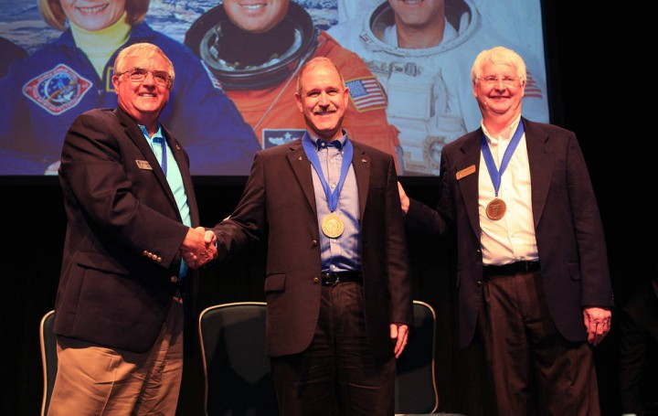 NASA Associate Administrator for the Science Mission Directorate and astronaut John Grunsfeld (center) is inducted into the U.S. Astronaut Hall of Fame on May 30, 2015 at the NASA Kennedy Space Center Visitor Complex in Florida. Shaking Grunsfeld's hand is Dan Brandenstein, Chairman of the board of directors for the Astronaut Scholarship Foundation, and standing next to Grunsfeld is former NASA astronaut Steve Hawley. Credits: NASA