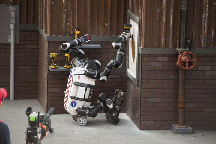 Using a cordless power drill, RoboSimian cuts a hole into a panel of drywall to complete one of the tasks in the DARPA Robotics Challenge Finals. Credits: JPL-Caltech