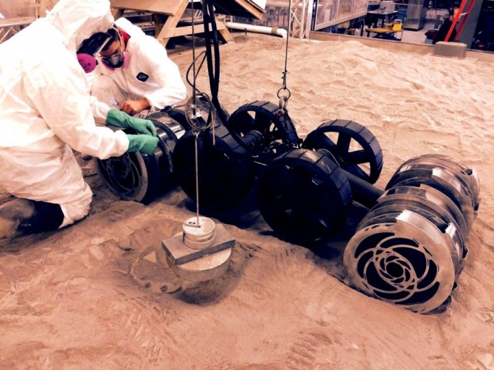Engineers make adjustments to the second generation Regolith Advanced Surface Systems Operations Robot prior to a test at the Kennedy Space Center's Swamp Works. As a resource, regolith shows promise for construction due to the extensive presence of basalt in the surface soil. The mineral is widespread among all igneous rocks and comprises more than 90 percent of all volcanic material and it is commonly found on both the moon and Mars. Credits: NASA