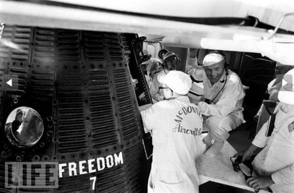 John Glenn crouches near Shepard's capsule, Freedom 7, along with technicians prior to launch. Credit: Ralph Morse/TIME & LIFE Pictures