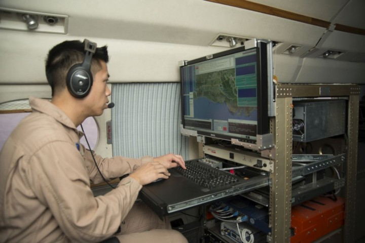Kean Tam, UAVSAR instrument operator, monitors the C-20A's flight path to ensure that accurate data are collected. Credits: NASA