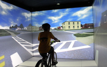 Kid on a stationary bike in the Hank Virtual Environments Lab The University of Iowa's Hank Virtual Environments Lab allows researchers to safely study the factors that put kids at risk when they're biking or walking across the street. Image credit: Hank Virtual Environments Laboratory at the University of Iowa