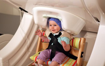 "University of Washington researchers found that by listening to various social interactions and exaggerated use of ""parentese,"" infants learn to program the motor movements needed to speak their native language and pay less attention to nonnative sounds. To make the discovery, infants sat in a brain scanner that measures brain activation through a noninvasive technique called magnetoencephalography as seen here. Image credit: Patricia Kuhl, Institure for Learning and Brain Sciences, University of Washington"