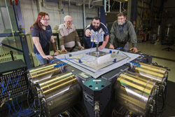 Sandia National Laboratories six-degrees-of-freedom vibration machine research team member Kevin Cross, second from right, adjusts accelerometer cables on a block head test item as, from left, Davinia Rizzo, David Smallwood and Norman Hunter watch. The team is working with a new type of large vibration machine capable of shaking test items in multiple directions simultaneously. The block head is a dynamically active structure designed to challenge the team's ability to control a complex system.