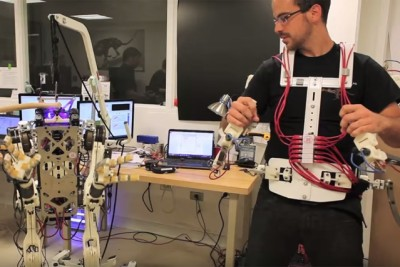 PhD student Joao Ramos demonstrates the Balance Feedback Interface, a system that enables an operator to control the balance and movements of a robot, through an exoskeleton and motorized platform.  Photo: Melanie Gonick/MIT