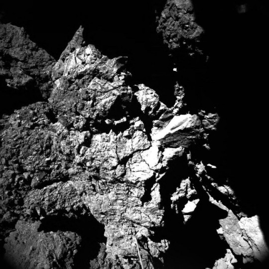 This well-lit image was acquired by Philae's CIVA camera 4 at the final landing site Abydos, on the small lobe of Comet 67P/Churyumov–Gerasimenko, on 13 November 2014. The image shows one of the CONSERT antennas in the foreground, which seems to be in contact with the nucleus. The dimensions of the antenna, 5 mm in diameter and 693 mm long, help to provide a scale to the image. The pebble-like features, blocks and cliffs observed in the CIVA images corresponds to what has been seen at larger scales from orbit. A large range of brightness is also seen, perhaps associated with different mineral compositions. Copyright ESA/Rosetta/Philae/CIVA