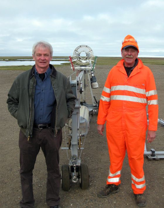 Sandia researcher Mark Ivey, left, and Sandia safety-basis engineer Al Bendure stand next to a folded SkyHook unmanned-aircraft catcher at Oliktok Point. The Arctic tundra stretches out behind them. (Photo courtesy of Brian O'Kronley, Fairweather LLC)