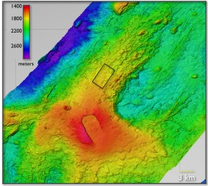 The eruption occurred inside the black rectangle, northwest of the main caldera (red) of Axial Volcano. The volcano rises about a half-mile from the seafloor, in ocean water about a mile deep. Image credit: NSF-OOI/UW/ROPOS