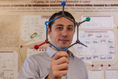 Bogdan Fedeles holds up a model of 5-chlorocytosine, a mutagenic DNA lesion occurring in inflamed tissues that may explain the link between chronic inflammation and cancer. Photo: Jose-Luis Olivares/MIT