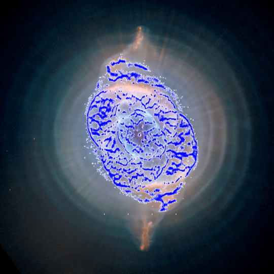 The planetary nebula known as Cat's Eye Nebula or NGC 6543, as observed with the Hubble Space Telescope (background image) and with ESA's Gaia satellite (blue points). It is located some 3000 light-years from us. Planetary nebulae are formed when the outer layers of an aging low-mass star are ejected and interact with the surrounding interstellar medium, leaving behind a compact white dwarf. Between July and August 2014, as Gaia performed many subsequent observations of a few patches of the sky close to the ecliptic poles, the satellite made over 200 observations of the Cat's Eye Nebula, located close to the north ecliptic pole. While doing so, Gaia registered over 84 000 detections that accurately trace out the intricate gaseous filaments that such objects are famous for. Copyright NASA/ESA/HEIC/The Hubble Heritage Team/STScI/AURA (background image); ESA/Gaia/DPAC/UB/IEEC (blue points)
