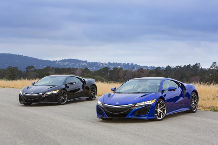 Two new Acura NSXs in Berlina Black and Nouvelle Blue. Powered by a 3.5-liter twin-turbocharged V-6 engine and three electric motors, new NSX will try to beat the performance of the best modern supercars and still be very efficient and reliable. Image credit: hondanews.com