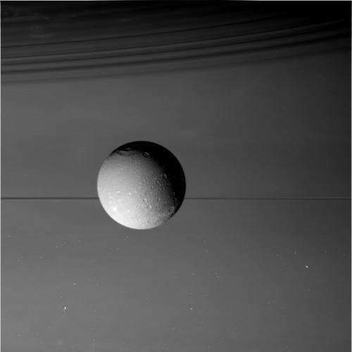 Dione in profile against Saturn. Image credit: NASA/JPL-Caltech/Space Science Institute