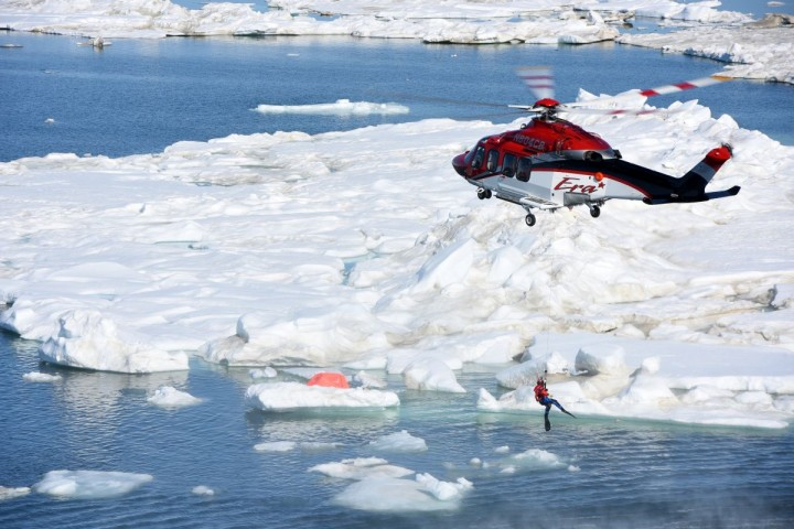 A helicopter crew lowers a swimmer into the Arctic Ocean during a search-and-rescue exercise near Oliktok Point, Alaska, July 13, 2015. The exercise, which involved unmanned aircraft systems and multiple participants, took place in the warning area under the stewardship of Sandia National Laboratories. (Photo by Coast Guard Petty Officer 2nd Class Grant DeVuyst)