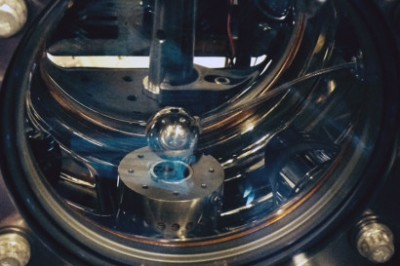 The vacuum chamber of the atom interferometer contains a one-inch diameter aluminum sphere. If chameleons exist, cesium atoms would fall toward the sphere with a slightly greater acceleration than their gravitational attraction would predict. Image credit: Holger Muller photo