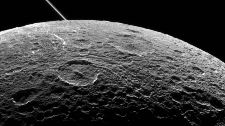 A view of Saturn's moon Dione captured by NASA's Cassini spacecraft during a close flyby on June 16, 2015. The diagonal line near upper left is the rings of Saturn, in the distance. Credits: NASA/JPL-Caltech/Space Science Institute